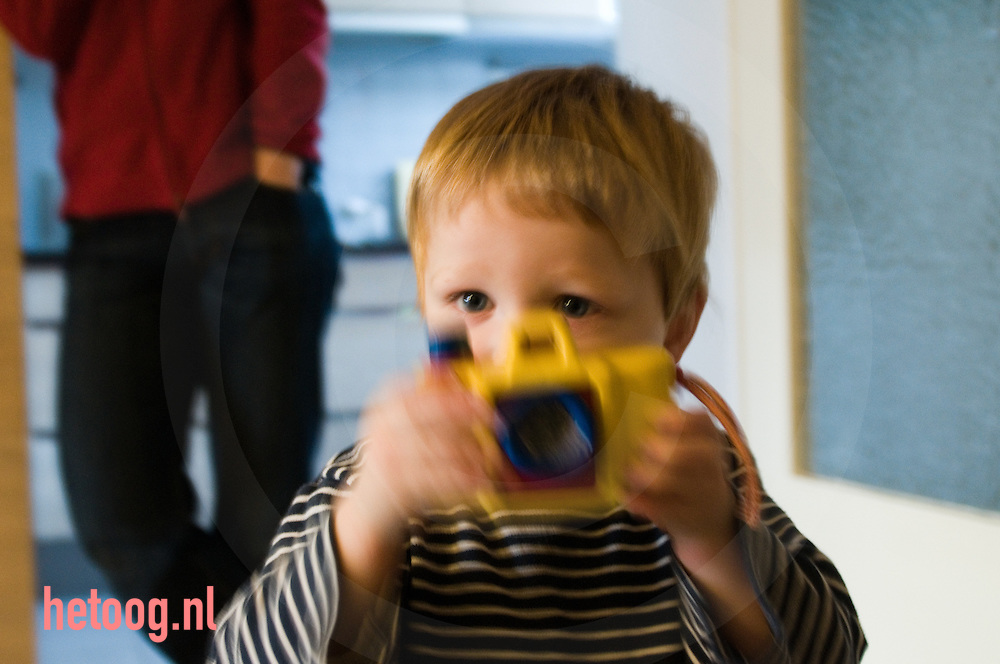 peuter speelt met een plastic speelgoed camera.