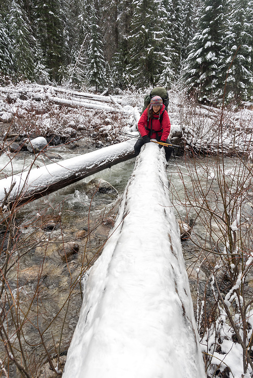 Backpacker crossing stream on a snow covered log in Idaho's Selway - Bitterroot Wilderness.
