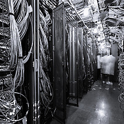 Inside the IceCube Laboratory at the South Pole.  There are over 5400 sensors in total looking for light stemming from high-energy particles created from cosmic ray or neutrino interactions.  Some of the cables, one for each light sensor, that feed data to a central computer are visible in this picture.  The IceCube observatory is remarkably robust, taking data with 99.9% uptime.  Occasionally, something does need maintenance or repair.  That means a trip of about 800 meters from the station to the IceCube Laboratory to track down the component that needs attention.