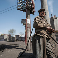 Coal day laborer Xiao Song waits on the outskirts of Taiyuan, Shanxi province with his shovel advertising his trade.