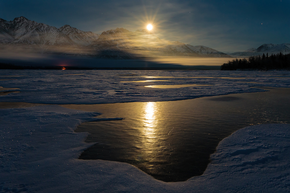 A full moon rises over the Chugach Mountains and the Knik River in Southcentral Alaska. Winter. Evening.