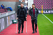 Craig Halkett (#26) (on crutches) of Heart of Midlothian FC and Jake Mulraney (#11) of Heart of Midlothian FC arrives before the Ladbrokes Scottish Premiership match between Heart of Midlothian and Rangers FC at Tynecastle Park, Edinburgh, Scotland on 20 October 2019.