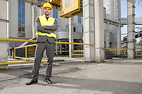 Portrait of young male architect standing arms crossed outside industry