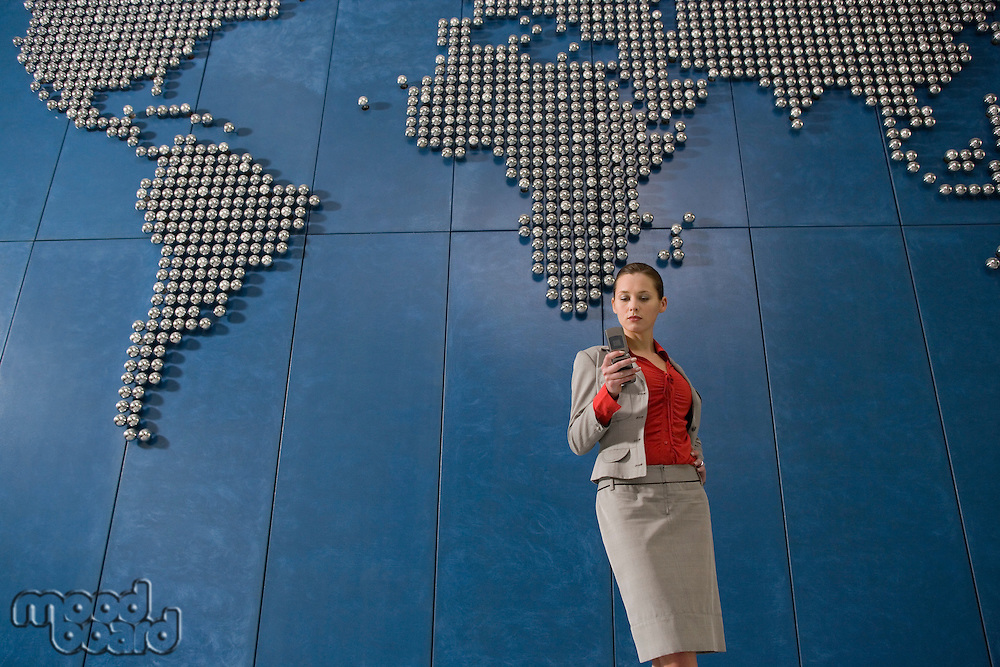 Business woman text messsaging using mobile phone in front of world map in office