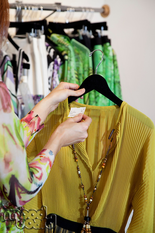 Young woman looking at price tag of a dress in clothing store