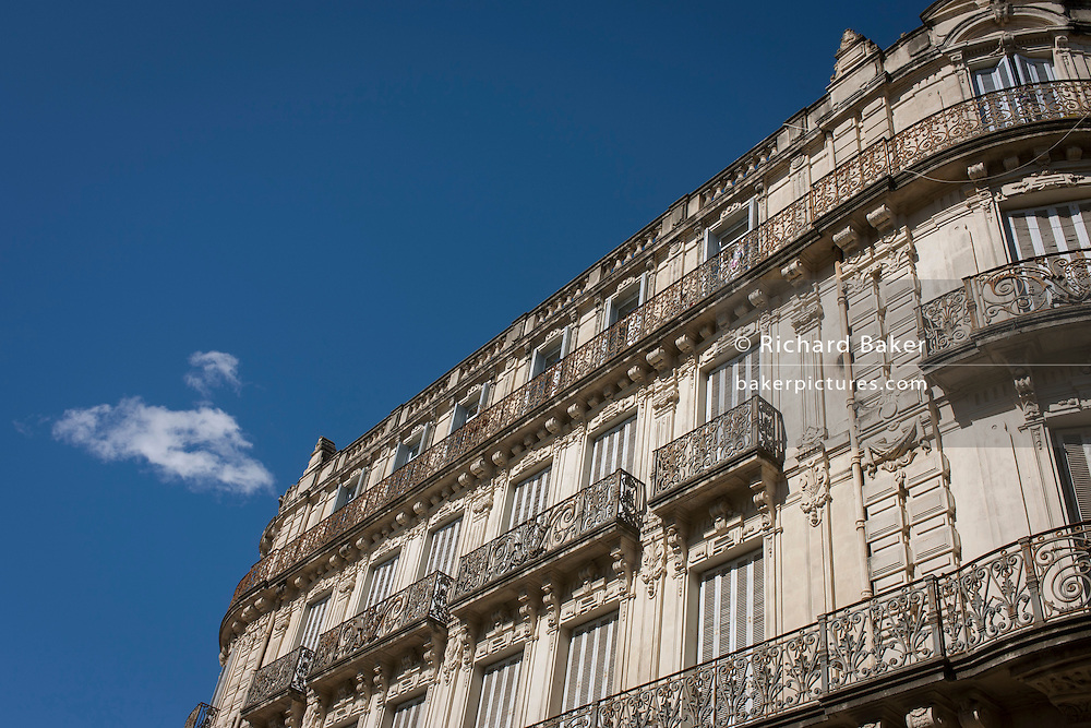 Architecture of apartments with ornate iron railings on Rue Foch in Montpellier, south of France.