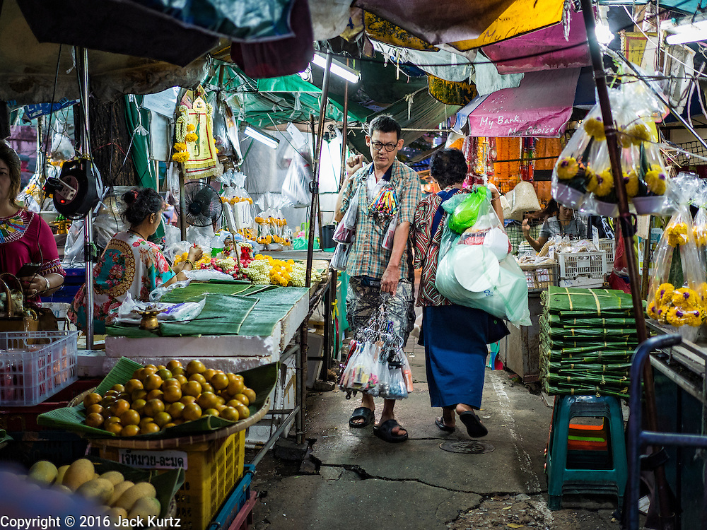 24 FEBRUARY 2016 - BANGKOK, THAILAND: A man peddling household supplies walks past sidewalk vendors in front of Pak Khlong Talat in Bangkok. Bangkok government officials announced this week that vendors in Pak Khlong Talat, Bangkok's well known flower market, don't have to move out on February 28. City officials are trying to clear Bangkok's congested sidewalks and they've cracked down on sidewalk vendors. Several popular sidewalk markets have been closed in recent months and the sidewalk vendors at the flower market had been told they would be evicted at the end of the month but after meeting with vendors and other stake holders city officials relented and said vendors could remain but under stricter guidelines regarding sales hours. The flower market is one of the best known markets in Bangkok and has become a popular tourist destination.        PHOTO BY JACK KURTZ