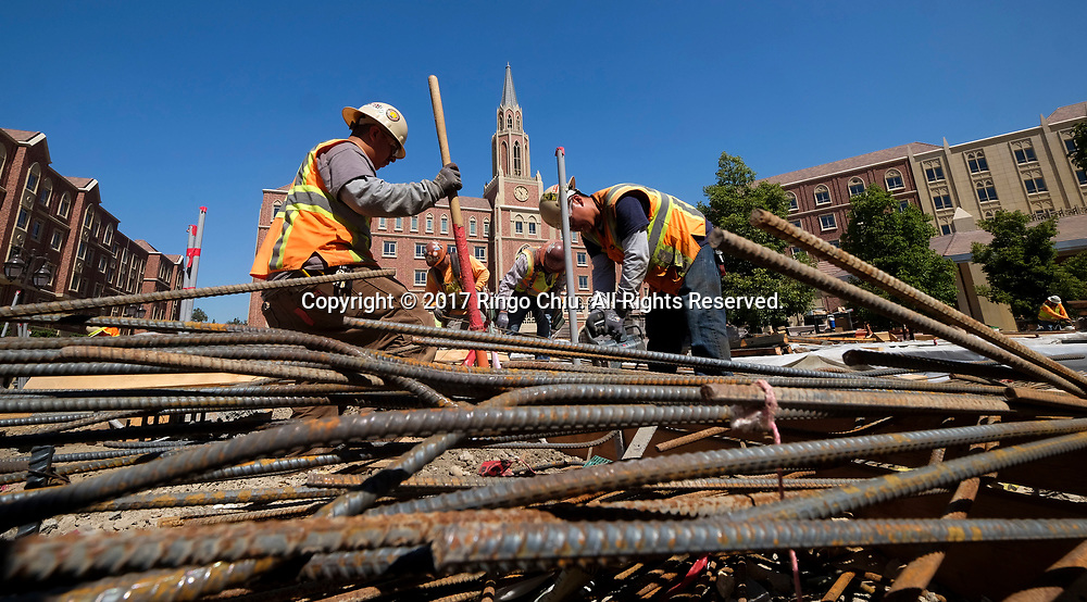 Workers in USC's University Village. USC's $700 million shopping and residential complex is nearly complete and more than a dozen retailers (Trader Joe's, Target, Starbucks, etc.) are set to open in August. (Photo by Ringo Chiu)<br /> <br /> Usage Notes: This content is intended for editorial use only. For other uses, additional clearances may be required.