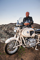 Brent Greenwood (MR) standing next to his 1960s BMW R60US motorcycle (PR) on the side of a country road in Sonoma County California.
