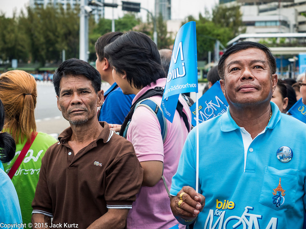 16 AUGUST 2015 - BANGKOK, THAILAND: People stand on a Bangkok street and wait for the ''Ride For Mom'' to start. More than 100,000 people across Thailand participated in the Bike For Mom event in honor of Queen Sirikit, who celebrated her 83rd birthday August 12. In Bangkok, the ride was led by His Royal Highness Crown Prince Maha Vajiralongkorn, the Crown Prince of Thailand and Sirikit's only son. Queen Sirikit, who is in poor health and living in a hospital, was unable to attend the bike ride.     PHOTO BY JACK KURTZ