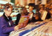 A group of girls looking at Ragga records, record shop, London, U.K 1990's.