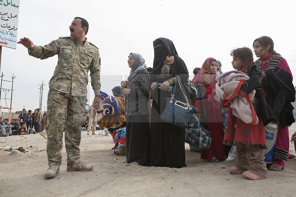 Licensed to London News Pictures. 10/11/2016. Mosul, Iraq. Guided by an Iraqi Army major women and children, all escaping from areas within Mosul where fighting between Iraqi Security Forces and Islamic State militants are fighting, board a bus in the city's Gogjali District. The bus, provided by the Iraqi Army, will take them to the safety of a refugee camp in Iraqi-Kurdistan.<br /> <br /> The battle to retake Mosul, which fell June 2014, started on the 16th of October 2016 with Iraqi Security Forces eventually reaching the city on the 1st of November. Since then elements of the Iraq Army and Police have succeeded in pushing into the city and retaking several neighbourhoods allowing civilians living there to be evacuated - though many more remain trapped within Mosul. Photo credit: Matt Cetti-Roberts/LNP