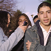 Teenagers on the streets one of them looking to the camera the others checking the phone, Cardiff 2000's