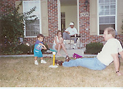 Marco hitting off a Tee (around 2 yeas old) with his Mom, Dad and Uncle Rick