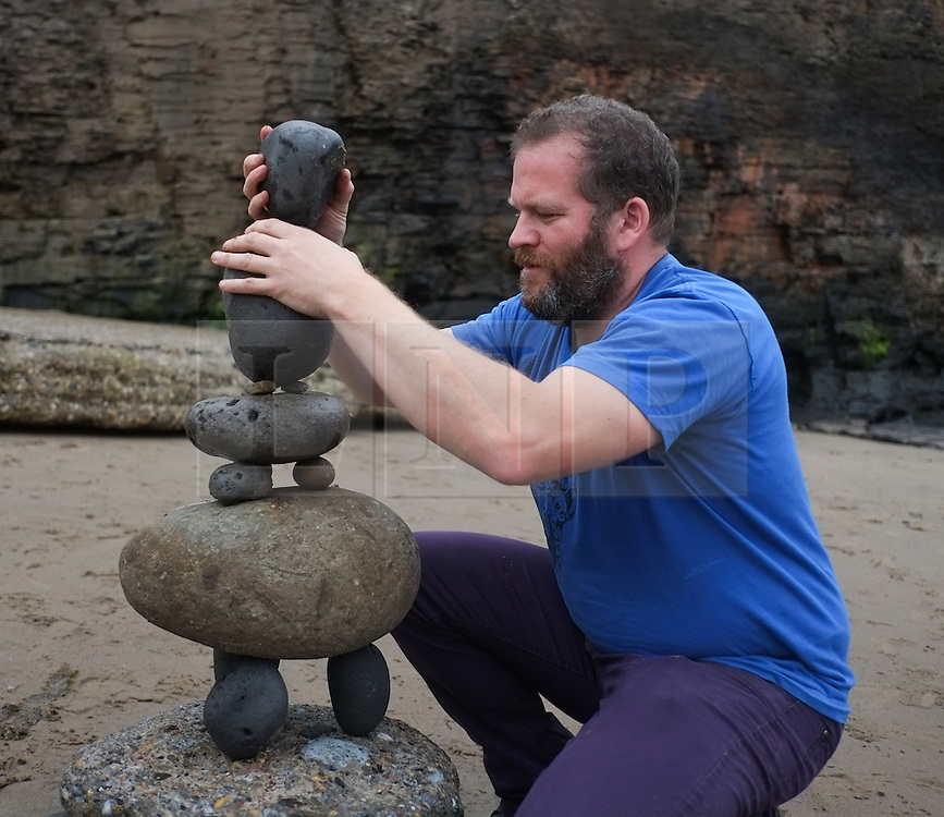 © Licensed to London News Pictures. <br /> 28/09/2014. <br /> <br /> Sandsend, United Kingdom<br /> <br /> Beach artist and stone balancer James Brunt creates a display during a sand art event held on the beach at Sandsend near Whitby. The event which took place as the tide dropped was short lived and was lost forever once the tide came back in.<br /> <br /> Photo credit : Ian Forsyth/LNP