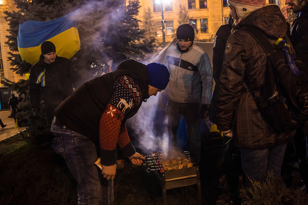 KIEV, UKRAINE - DECEMBER 3: Protesters grill meat during an ongoing anti-government rally in Independence Square on December 3, 2013 in Kiev, Ukraine. Thousands of people have been protesting against the government since a decision by Ukrainian president Viktor Yanukovych to suspend a trade and partnership agreement with the European Union in favor of incentives from Russia. (Photo by Brendan Hoffman/Getty Images) *** Local Caption ***