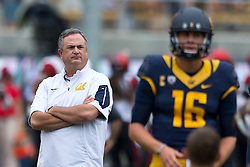 BERKELEY, CA - SEPTEMBER 12:  Head coach Sonny Dykes of the California Golden Bears watches quarterback Jared Goff #16 warm up before the game against the San Diego State Aztecs at California Memorial Stadium on September 12, 2015 in Berkeley, California. The California Golden Bears defeated the San Diego State Aztecs 35-7. (Photo by Jason O. Watson/Getty Images) *** Local Caption *** Sonny Dykes; Jared Goff