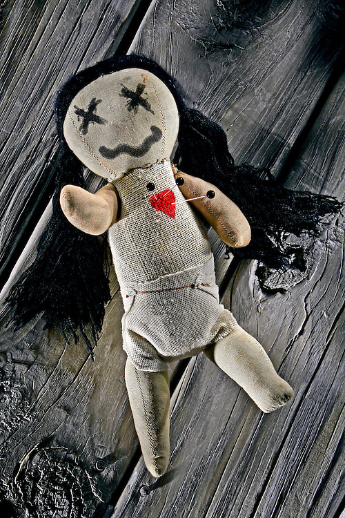 A voodoo doll laying on old weathered wood planks has three black pins stuck into its heart.
