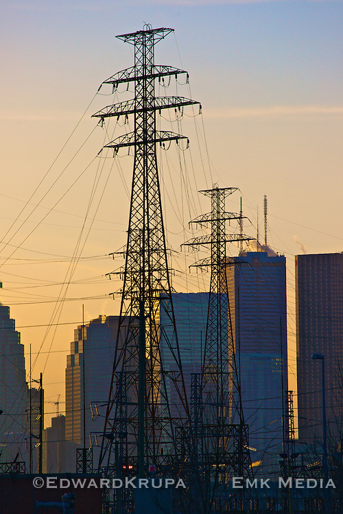 Electriciy pylons, or transmission towers, loom over city at sunset. Toronto, ON.