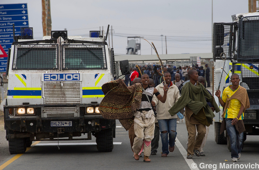 Marikana, North West Province, South Africa. September 5, 2012. Striking Marikana Lonmin miners leaders retiurn from delivering their ultimatum to Lonmin after they marched to Karree mine.  They hold up the image of mambush, one of the strike leaders killed by police. Photo Greg Marinovich