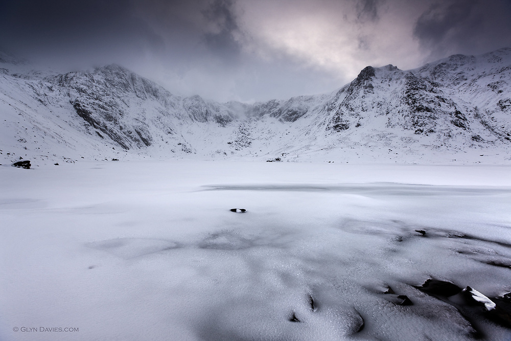 The immesely popular and beautiful Cwm Idwal in Snowdonia looks far more hostile in the depth of winter, when the normally shimmering surface of Llyn Idwal lake is deceptively soft and pristine under an icy cover, disgusing it's black depths.