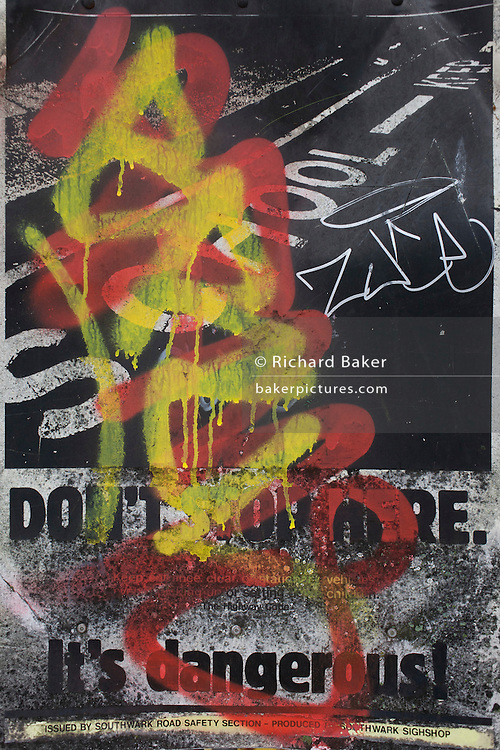 Graffiti covering a Do Not Park sign, outside a Dulwich school, London borough of Southwark.
