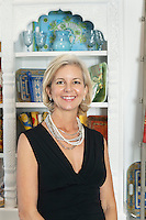 Portrait of mature woman smiling while standing in front of shelves