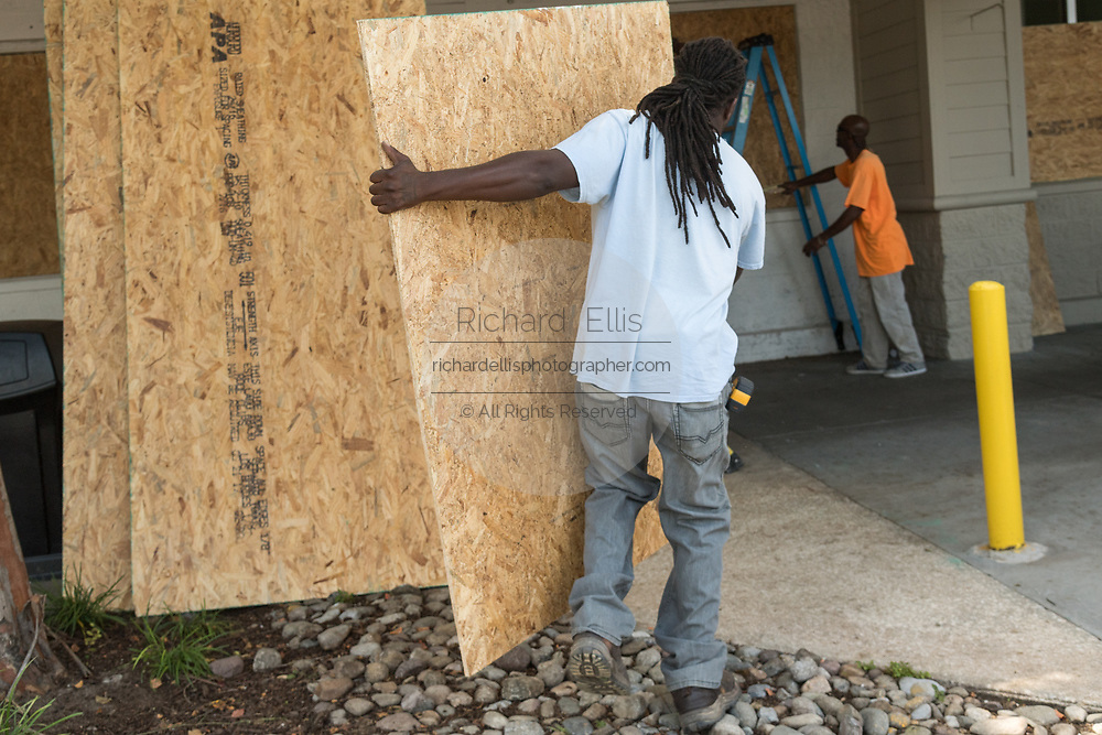 Workers board up windows at a Whole Foods Market in preparation for Hurricane Irma September 8, 2017 in Mount Pleasant, South Carolina. Imra is expected to spare the Charleston area but hurricane preparations continue as Irma leaves a path of destruction across the Caribbean.