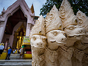10 JULY 2018 - NAKHON PATHOM, THAILAND:  People pray at the main Buddha statue in Phra Pathom Chedi in Nakhon Pathom. Nakhon Pathom is about 35 miles west of Bangkok. It is one of the oldest cities in Thailand, archeological evidence suggests there was a settlement on the site of present Nakhon Pathom in the 6th century CE, centuries before the Siamese empires existed. The city is widely considered the first Buddhist community in Thailand and the nearly 400 foot tall Phra Pathom Chedi is considered the first Buddhist temple in Thailand.    PHOTO BY JACK KURTZ