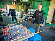 """28 OCTOBER 2014 - BANGKOK, THAILAND: A worker covers the lid of the oven in hot coals at the Pajonglak Maneeprasit Bakery in Bangkok. The cakes are called """"Kanom Farang Kudeejeen"""" or """"Chinese Monk Candy."""" The tradition of baking the cakes, about the size of a cupcake or muffin, started in Siam (now Thailand) in the 17th century AD when Portuguese Catholic priests accompanied Portuguese soldiers who assisted the Siamese in their wars with Burma. Several hundred Siamese (Thai) Buddhists converted to Catholicism and started baking the cakes. When the Siamese Empire in Ayutthaya was sacked by the Burmese the Portuguese and Thai Catholics fled to Thonburi, in what is now Bangkok. The Portuguese established a Catholic church near the new Siamese capital. Now just three families bake the cakes, using a recipe that is 400 years old and contains eggs, wheat flour, sugar, water and raisins. The same family has been baking the cakes at the Pajonglak Maneeprasit Bakery, near Santa Cruz Church, for more than 245 years. There are still a large number of Thai Catholics living in the neighborhood around the church.   PHOTO BY JACK KURTZ"""
