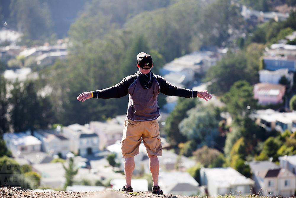 Een man geniet op de top van Twin Peaks van de wind en het uitzicht. De Amerikaanse stad San Francisco aan de westkust is een van de grootste steden in Amerika en kenmerkt zich door de steile heuvels in de stad.<br /> <br /> At the summit of Twin Peaks a man enjoys the wind and view. The US city of San Francisco on the west coast is one of the largest cities in America and is characterized by the steep hills in the city.