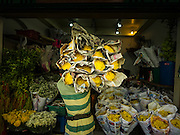"""11 AUGUST 2016 - BANGKOK, THAILAND: A delivery of flowers to a florist shop in Pak Khlong Talat. Pak Khlong Talat (literally """"the market at the mouth of the canal"""") is the best known flower market in Thailand. It is the largest flower market in Bangkok. Most of the shop owners in the market sell wholesale to florist shops in Bangkok or to vendors who sell flower garlands, lotus buds and other floral supplies at the entrances to temples throughout Bangkok. There is also a fruit and produce market which specializes in fresh vegetables and fruit on the site. It is one of Bangkok's busiest markets and has become a popular tourist attraction.         PHOTO BY JACK KURTZ"""
