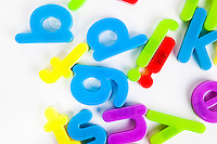 Close-up view of disordered alphabet magnets on white background