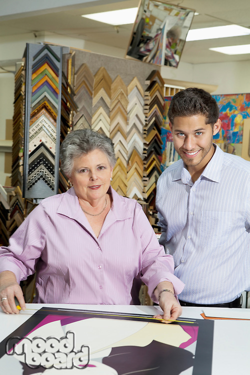Portrait of senior female owner with customer measuring picture frame