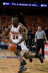Virginia's Mamadi Diane (24) dribbles past a Wake Forest defender.  The Virginia Cavaliers defeated the Wake Forest Demon Decons 88-76 at the John Paul Jones Arena in Charlottesville, VA on January 21, 2007.