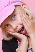 Portrait of a surprise young girl with hands on face over pink background