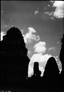 A stone lion crouches between the towers of East Mebon.