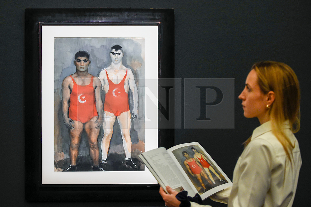 "© Licensed to London News Pictures. 22/11/2019. LONDON, UK. A staff member views ""Wrestlers"", 1933, by Vladmir Lebedev (Est. GBP30-50k) at the preview for the upcoming sales of Russian artworks at Sotheby's New Bond Street.  The Russian Pictures and Works of Art, Fabergé and Icons sales take place on 26 November.  Photo credit: Stephen Chung/LNP"