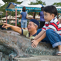 A boy sitting on a bronze dragon statue set along the Kuching waterfront. The  Sarawak River separates the north and the south of Kuching.