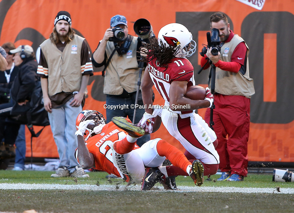 Arizona Cardinals wide receiver Larry Fitzgerald (11) appears to injure his right foot as he catches a 6 yard fourth quarter touchdown pass that gives the Cardinals a 31-20 lead while covered by Cleveland Browns cornerback Johnson Bademosi (24) during the 2015 week 8 regular season NFL football game against the Cleveland Browns on Sunday, Nov. 1, 2015 in Cleveland. The Cardinals won the game 34-20. (©Paul Anthony Spinelli)