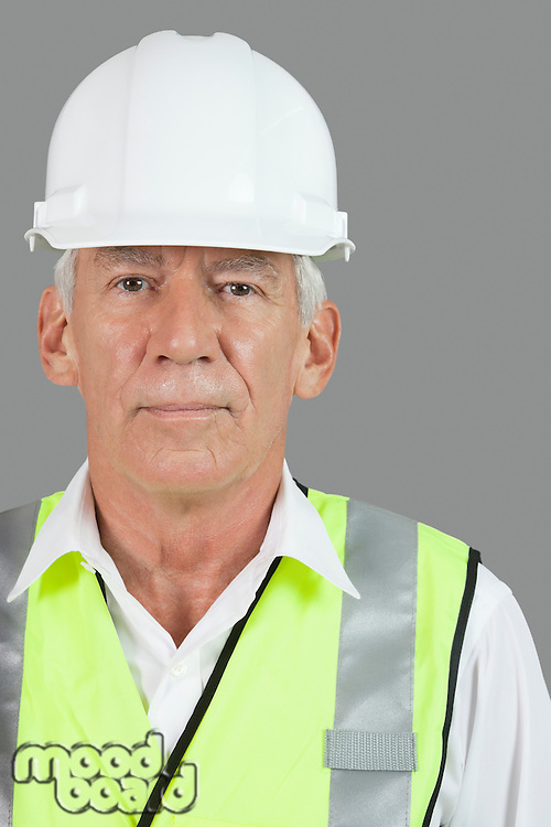 Portrait of male senior construction worker wearing hard hat over white background