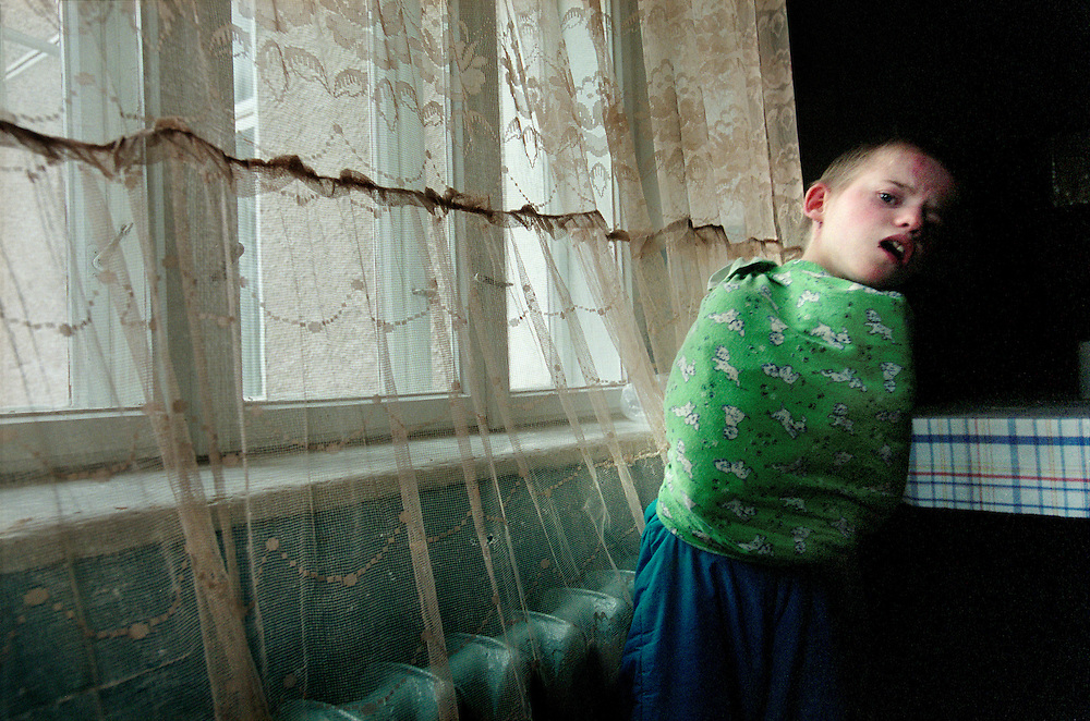Chernobyl Legacy. ..Ukraine 2001...Children that no one wants live in an orphanage in Zaluzhya. Many of the children here who were born shortly after the Chernobyl accident are sick and show sympthoms that could be related to radiation, but most of them have never met a doctor. The orphange have very small fundings and is constantly understaffed...A child wears a straitjacket in bright colors. The staff don't have time to tend to him and makes children who scratch themselves or hit others wear this kind of device...Photo: Markus Marcetic/MOMENT..