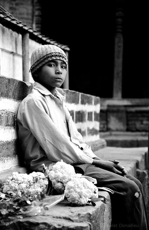 Un jeune garçon assis sur les marches d'un temple, attend de vendre ses choux. Bhaktapur, Népal. 2008