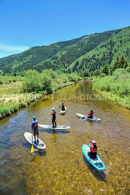 "Stand up paddleboarders navigate the Roaring Fork River near the North Star Nature Preserve just east of Aspen, Colorado during the 2012 ""Outside in Aspen"" event."
