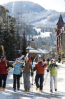 A group of skiers laugh with each other as they walk through Whistler Village on a sunny winter day.