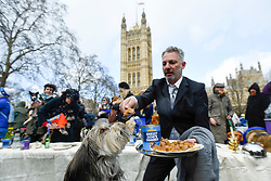 "© Licensed to London News Pictures. 10/03/2019. LONDON, UK. A dog being fed as Pro-Remain owners bring their dogs to Victoria Park Gardens, next to the Houses of Parliament, for ""Brexit is a Dog's Dinner"", a protest to urge MPs to vote to ensure that a no-deal Brexit is avoided and to give the people of the UK a final say.  Next week, there will be a series of up to three votes in the House of Commons where MPs will vote on whether to accept Theresa May's Brexit deal.  Photo credit: Stephen Chung/LNP"