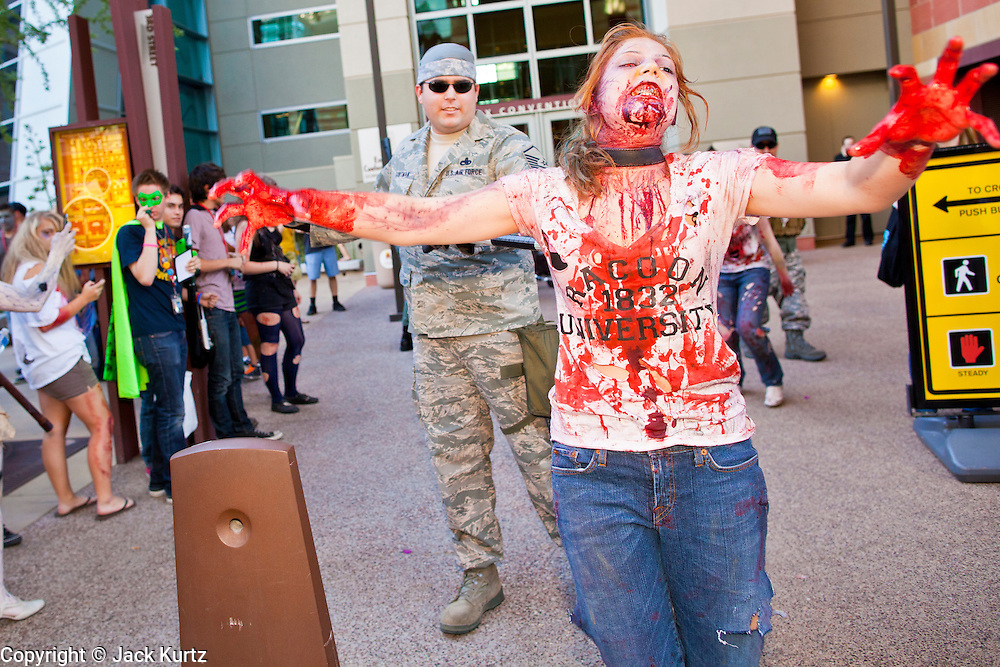 "27 MAY 2011 - PHOENIX, AZ: A chained and leashed ""zombie"" is escorted through downtown Phoenix by a ""soldier"" during the Comicon Zombie Walk Friday. Phoenix Comicon opened Thursday and featured a Zombie Walk through downtown Phoenix Friday night. Hundreds of people participated in the Zombie Walk, both as Zombies and as Zombie hunters. This year's Comicon includes appearances by Leonard Nimoy (Star Trek), Adam Baldwin (Firefly and Chuck), Stan Lee (Marvel Comics), Nicholas Brendon (Buffy the Vampire Slayer) and others. Activities include costuming workshops, role playing games and a Geek Prom.     Photo by Jack Kurtz"