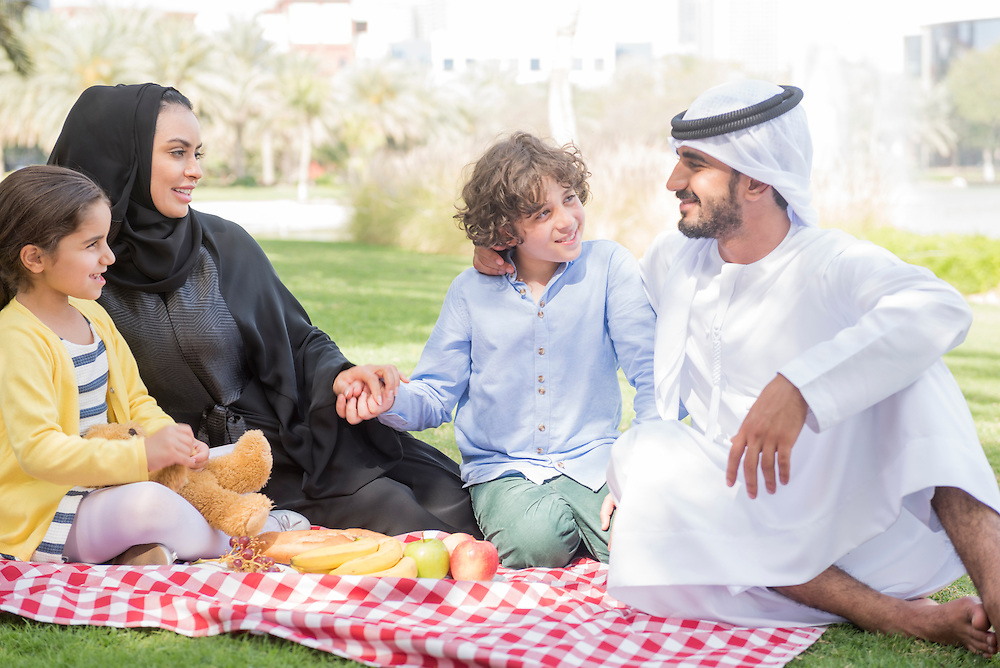 Happy smiling Emirati Arab family enjoying a picnic on sunny day in Dubai, United Arab Emirates. Mother, father with children -  little girl and boy sitting together outdoors.