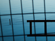 Reflection of a fence mostly submerged in water.  A barrier and a wire fence is in the foreground, creating an abstract composition in blue.  At The Lake, Central Park, New York City.