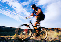 Blur shot of a man riding a mountain bike in a desert canyon.  Frenchmans Coulee near Vantage, Washington, USA